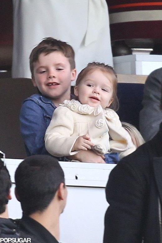 Cậu út Cruz để Harper ngồi vào lòng mình trong khi xem bố chơi bóng đá.