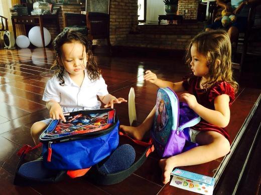 Hai nhóc thích thú với cặp sách đi học.