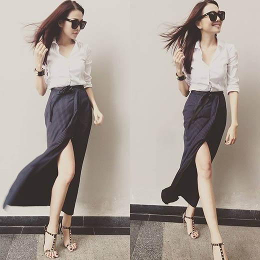 Chiếc áo sơ mi trắng cổ điển được Thanh Hằng làm mới khi kết hợp cùng chân váy kẻ sọc, xẻ tà. Giày cao gót chiến binh đính kim loại cùng chiếc mắt kính gọng vuông càng làm tăng thêm sự cá tính, mạnh mẽ cho nữ giám khảo quyền lực của VietNam's Next Top Model 2015.