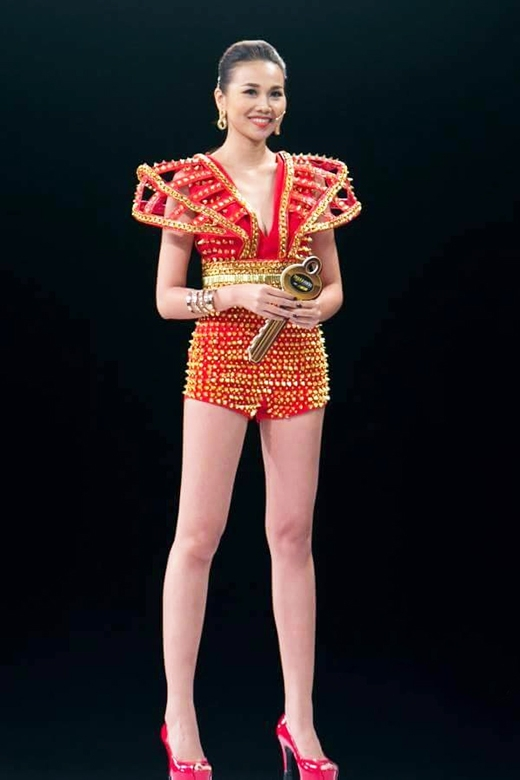 Trong phần ghi hình thử thách thí sinh trước khán giả, chân dài 1m12 diện bộ jumpsuit được dựng phom 3D khá độc đáo. Sắc đỏ ruby cùng những chi tiết đinh tán càng làm tăng thêm sự nổi bật, cá tính, quyền lực cho Thanh Hằng.