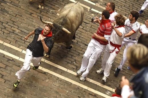 """Một người tham gia lễ hội Fan Fermin tại Pamplona, Tây Ban Nha đang chạy trước mũi chú bò dọc đường Mercaderes. Mỗi năm, du khách từ khắp nơi trên thế giới ghé thăm Pamplonađể góp mặt vào 8 ngày """"đấu bò"""" đầy kịch tính này."""