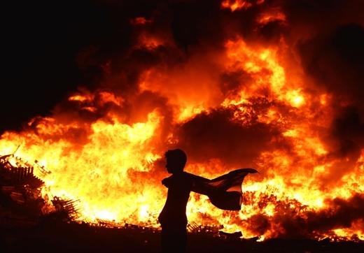 Một thành viên trẻ tuổi thuộc dòng dõi Hoàng gia mang lá cờ Union Jack của Vương quốc Anh đi qua đám lửa tại New Mossley, Bắc Ireland. Những đám lửa này đánh dấu sự khởi đầu của lễ diễu hành Orange thường niên, được tổ chức vào ngày 12/7.