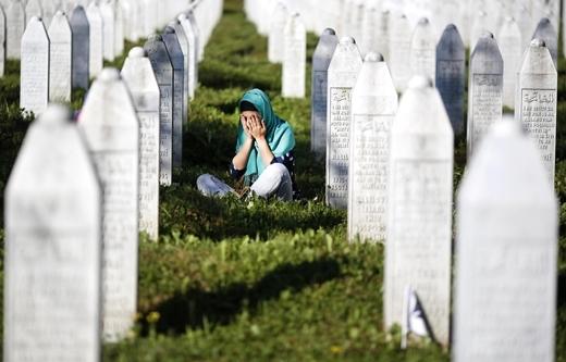 Một người phụ nữ than khóc trong ngôi mộ tại Đài tưởng niệm Trung tâm Potocari. Các lễ hội được tổ chức tại đây để đánh dấu kỉ niệm 20 năm vụ thảm sát Srebrenica.
