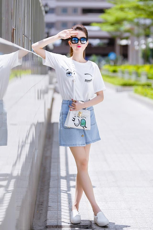 Ngọc Trinh diện chiếc áo họa tiết đôi mắt cùng quần jeans cạp cao, chân váy cài cúc giữa hợp mốt nhằm khoe khéo đôi chân dài.