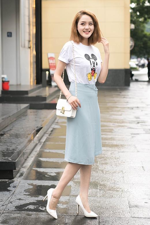 Cô chọn phối cùng áo phông in họa tiết chuột Mickey xinh xắn. Phụ kiện đi kèm gồm có túi đeo chéo, giày cao gót mũi nhọn tông trắng.