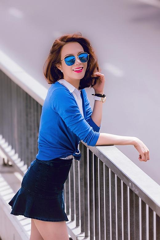 Sự duyên dáng, thanh lịch hòa trộn một chút nổi loạn, gợi cảm của những cô gái đôi mươi qua chân váy jeans kết hợp cùng sơ mi trắng và cardigan xanh coban khoác ngoài.