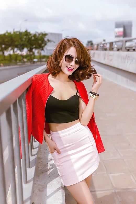 Chân váy midi tông hồng pastel dịu ngọt được chọn phối cùng áo crop-top hai dây nhằm khoe khéo vòng eo thon gọn.