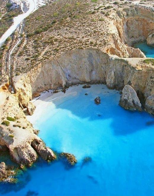 Vách núi đá sừng sững bao quanh vùng biển xanh trong.