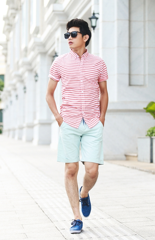 Áo sơ mi tay ngắn kết hợp cùng quần lửng vẫn chưa bao giờ lỗi mốt với nam giới. Nhưng bộ trang phục của Quang Đăng lại trông khá mới mẻ, lạ mắt bởi tông hồng của những đường kẻ sọc cùng sắc xanh lơ ngọt ngào.