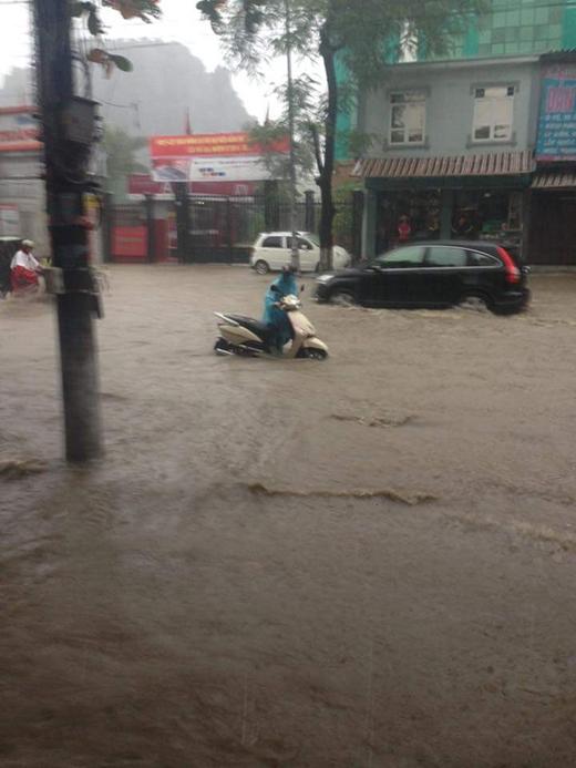 Người dân phải dắt xe trong biển nước.