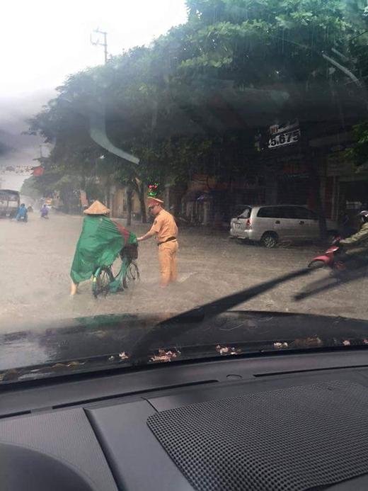 Do nhiều tuyến đường bị ngập nặng, lực lượng CSGT phải đội mưa ra đường phân luồng giao thông và giúp người dân.