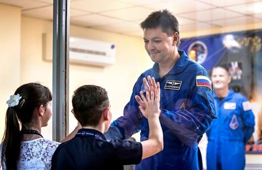 Một thành viên của phi hành đoàn Trạm vũ trụ quốc tế Oleg Kononenko của Nga đang chạm tay với những đứa con của mình thông qua tấm kiếng tại cuộc họp báo ở Cosmodrome Baikonur, Baikonur, Kazakhstan.