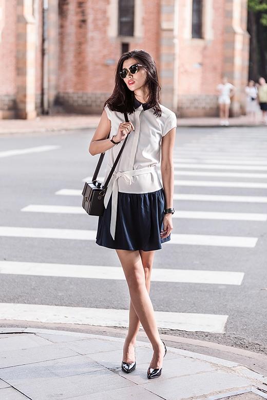 Chân dài Thiên Trang tiếp tục lăng xê mốt váy lấy phom từ áo sơ mi truyền thống. Tuy nhiên, thiết kế này lại khá lạ mắt bởi tùng váy xếp li điệu đà cùng chiếc thắt lưng nhằm khoe khéo vòng eo thon gọn.