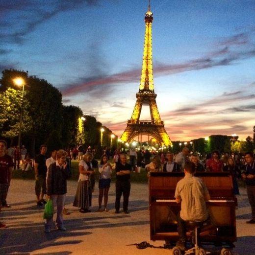 Dotan chơi đàn trước tháp Eiffel, Paris.
