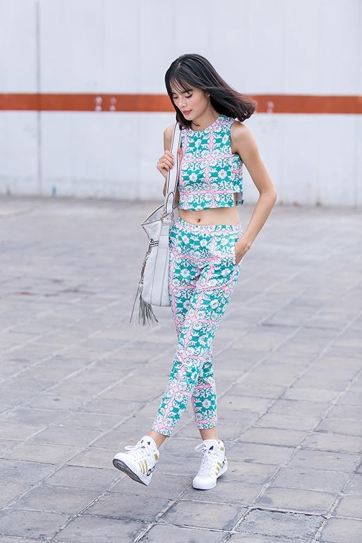 Sự kết hợp kinh điển của quần ôm ống côn cùng áo crop-top cổ điển lại mang đến cảm giác tươi trẻ bởi những họa tiết hoa trắng trên nền xanh ngọc.