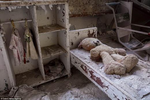 Phòng ngủ của một bé gái bị tàn phá, chỉ còn lại chú gấu bông nằm trên giường.