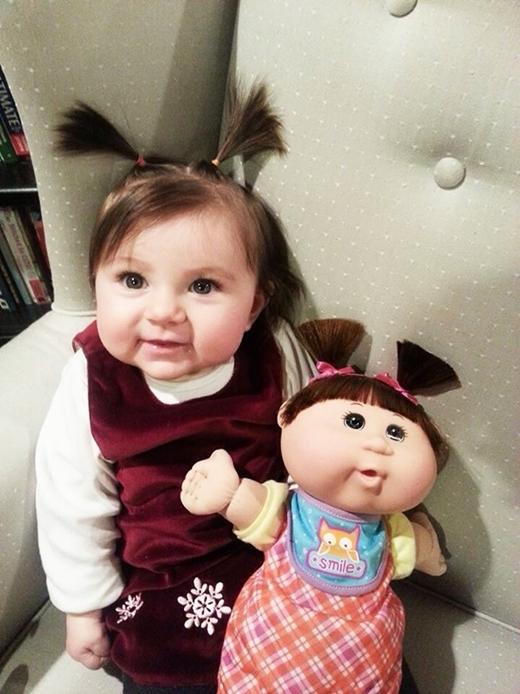 """Cách buộc tóc hai chùm nhí nhố và khuôn mặt phúng phính khiến cô bé này trông như """"chị em sinh đôi"""" với con búp bê của mình."""