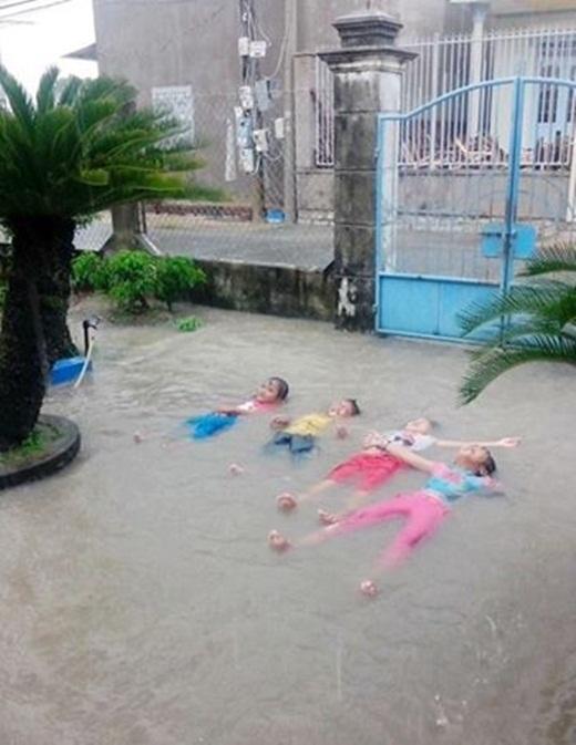 Tác giả của bức ảnh này đã nhanh tay ghi lại cảnh bốn đứa em nằm chơi đùa dưới cơn mưa lớn và chia sẻ lên mạng. Rất nhanh chóng, khoảnh khắc vui vẻ này đã nhận được rất nhiều sự chú ý của mọi người. Bốn đứa trẻ thả mình dưới khoảng sân ngập nước, không lo lắng mà chỉ vui vẻ với niềm thích thú riêng mình.