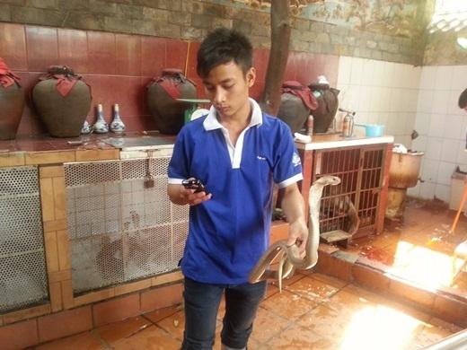 Nhân viên ở một quán ăn ở Việt Nam đang giữ một con rắn cho Gunnar chụp ảnh.
