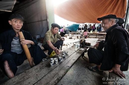 Những người đàn ông uống rượu và hút thuốc lào ở một phiên chợ.