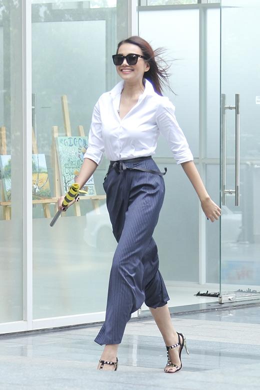Thanh Hằng mở màn chào đón thí sinh trong bộ trang phục kết hợp giữa chiếc áo sơ mi trắng cổ điển cùng chân váy maxi sọc xanh xám nhằm khoe khéo đôi chân dài gợi cảm.