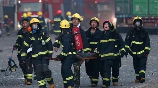 Hình ảnh những người lính cứu hỏa cấp tốc khiêng thi thể một nạn nhân từ trong vụ nổ đi ra. Họ đều mang vẻ mặt khẩn trương.