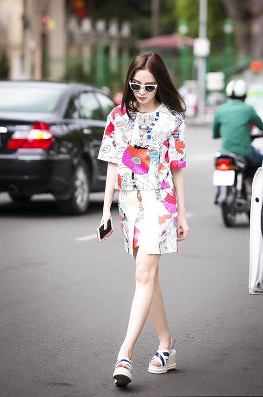 Angela Phương Trinh khéo léo giấu đường cong trong chiếc áo phom rộng phối cùng chân váy midi. Họa tiết hoa lá với tông màu nổi bật như mang đến một luồng gió mới cho bức tranh thời trang mùa thu khá trầm mặc, sâu lắng.