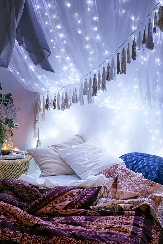 Nếu bạn sở hữu một chiếc giường ngủ kiểu công chúa có những tấm màn che phía trước, hãy dùng những dây đèn LED để mắc lên tấm màn. Buổi tối, bạn sẽ như chìm vào một không gian vô cùng thơ mộng. Hoặc bạn cũng có thể tạo ra một chiếc màn độc đáo bằng cái vòng lắc hông, tấm màn và vài sợi dây ruy băng để cố định lên trần nhà.