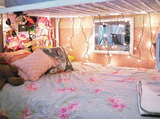 Nếu bạn ở trong kí túc xá và phải ngủ ở giường tầng dưới, hãy tận dụng những thanh chắn của chiếc giường phía trên để mắc các dây đèn trang trí cho thêm lung linh như thế này nhé.