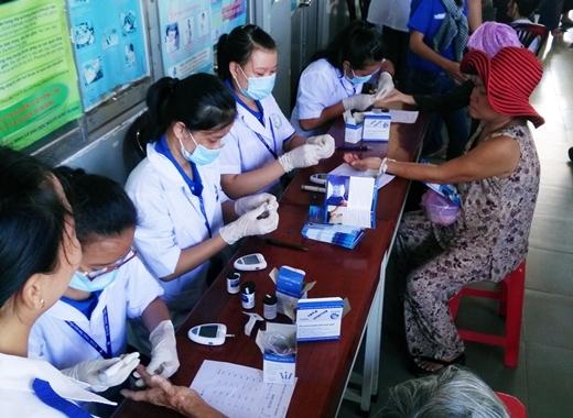 Người dân được sinh viên ĐH Y Dược đo huyết áp và kiểm tra đường huyết ngay trong lúc chờ đợi lượt khám của mình.