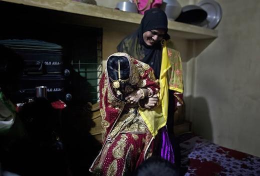 Cô dâuNasoin Akhtermiễn cưỡng để người bên gia đình chú rể bế lên giường chụp hình trong ngàycưới.