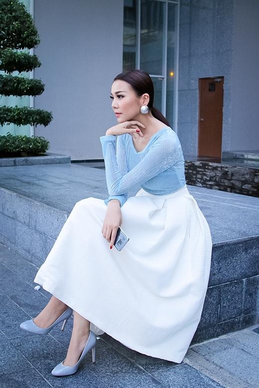 Sự kết hợp giữa chiếc áo phông cổ rộng tông xanh thiên thanh cùng chân váy xòe xếp li chữ A giúp Thanh Hằng trở nên điệu đà, nữ tính hơn.