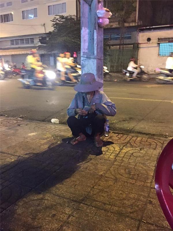 Cụ già bán vé số tội nghiệp ngồi ở góc cột điện.