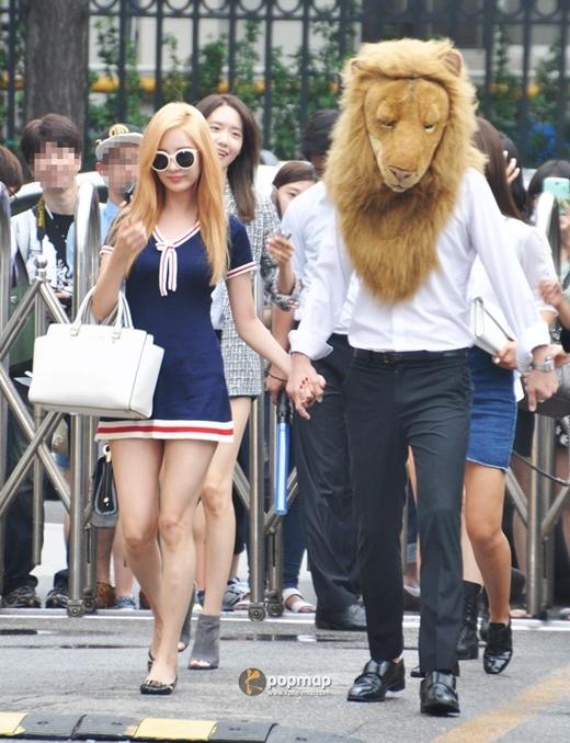"""Có lẽ trong lần trở lại này, nhân vật khiến các fan SNSD """"thấy ghét"""" nhất không ai khác chính là chú sư tử. Không chỉ được xuất hiện trên bìa album, MV… mà còn bước ra cả đời thực, sánh vai bên cạnh 8 cô gái xinh đẹp. Trong suốt chặng đường """"đi làm"""" tại Music Bank, anh chàng liên tục được các thành viên SNSD nắm tay dẫn lối, thậm chí còn tạo dáng chụp hình, khiến các fan vừa thích thú, vừa ganh tị."""