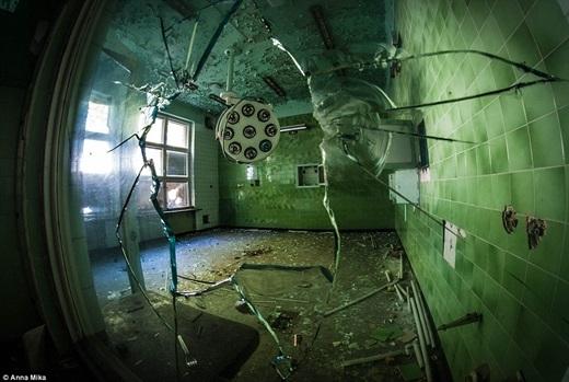 Nhờ khung cửa kính vỡ này mà Anna có thể nhìn vào bên trong bệnh viện cũ ở Ba Lan và phát hiện gạch vụn nằm vung vãi khắp nền nhà.