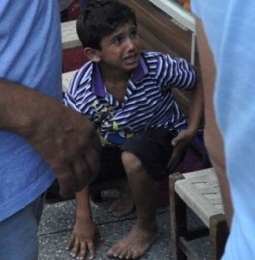 """Cậu bé này có tên làAhmet. Cậu bị chủ quán ăn đuổi đánh vì chỉ """"trót"""" mời khách mua giấy ăn từ cửa hàng của anh ta. Hình ảnh đáng thương của cậu béAhmetkhi bị đánh đập trên phố đã khiến người dân trên khắp thế giới thương cảm."""