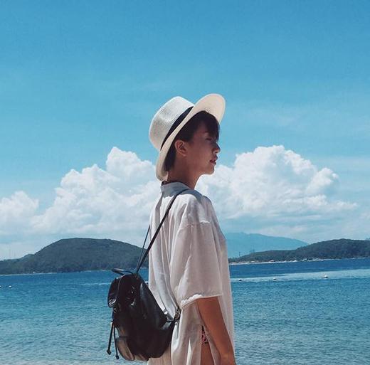 Quỳnh Anh Shyn với tông trắng nhẹ nhàng trước bầu trời và bãi biển xanh ngắt tuyệt đẹp của Nha Trang.