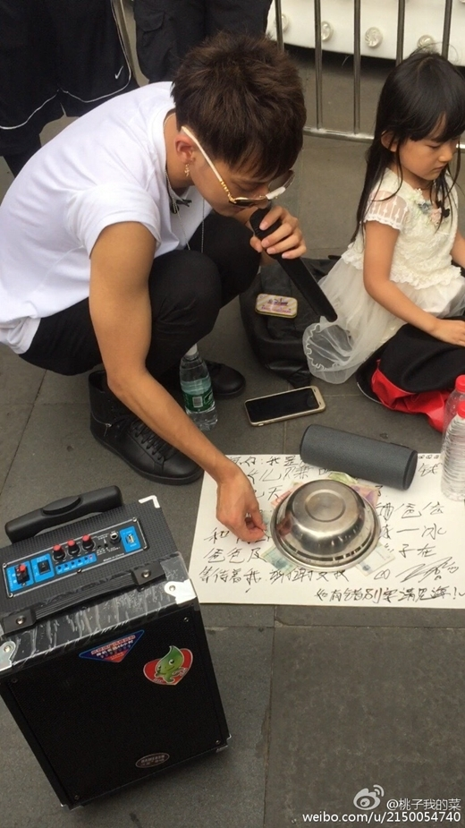 Tao viết trên giấy:  Xin chào mọi người, tôi là ông bố trẻ Hoàng Tử Tao đây. Tôi đang rất đói vì phải tiết kiệm tiền để mua pizza cho con gái.