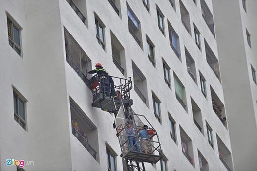 Xe thang vươn lên tầng 9 và cảnh sát cắt lưới kim loại để giải cứu người dân.