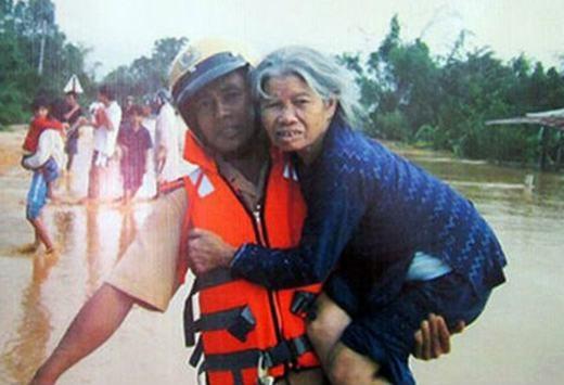 Một cảnh sát bế bà cụ thoát khỏi dòng nước triều cường. (Ảnh: Internet)