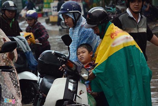 Người đàn ông đang hỗ trợ một phụ nữ có em bé suýt té ngã giữa dòng nước. (Ảnh: Zing)