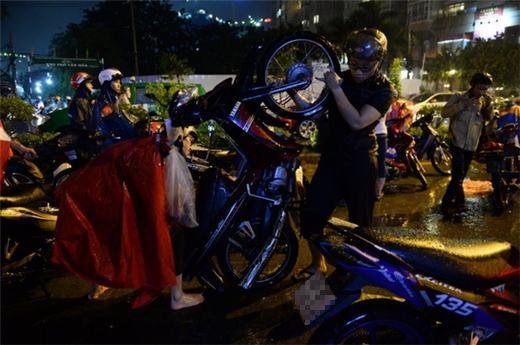 Một thanh niên đang giúp đỡ người phụ nữ dốc xe cho nước chảy ra khỏi ống pô xe máy. (Ảnh: Internet)