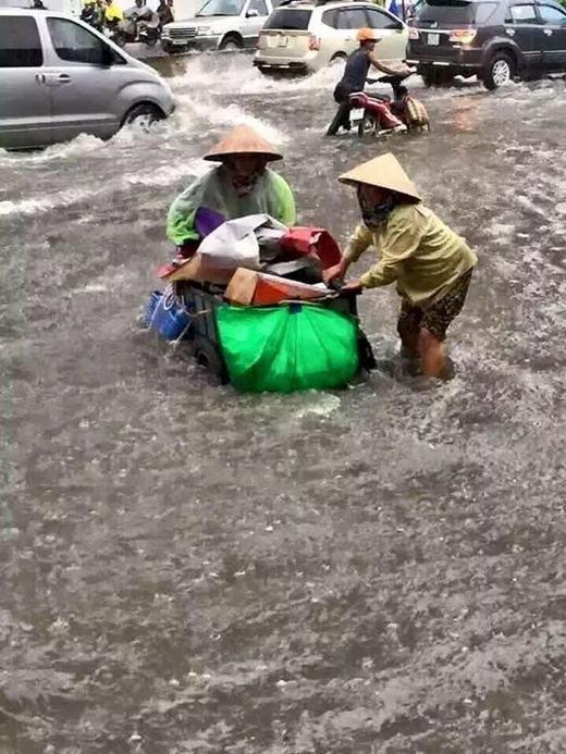 Mưa lớn khiến những người lao động càng thêm cực khổ. Trong hình là hai phụ nữ đang hỗ trợ nhau kéo chiếc xe đựng ve chai của mình đến nơi không ngập. (Ảnh: Internet)