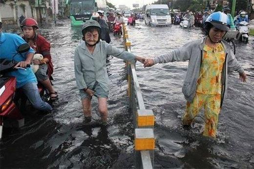 Bà cụ được một người phụ nữ dắt đi giữa dòng nước dù có lan can ở giữa. (Ảnh: Internet)
