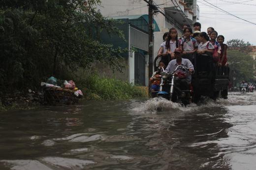 Một tài xế xe ba gác tình nguyện chở các em học sinh qua con đường ngập nước. (Ảnh: Internet)
