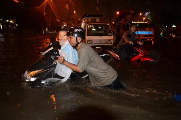 Một phụ huynh cố gắng đẩy chiếc xe và đứa con ra khỏi dòng nước lớn. Trong ảnh, đứa trẻ lạnh run rất tội nghiệp. Ảnh: TTO