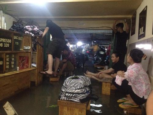 Khách vào quán cafe để tránh mưa cũng phải ngồi trên ghế vì nước ngập. Ảnh: VNE