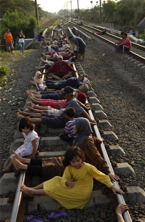 Cư dân già trẻ lớn bé ở vùng phía Tây Indonesia đang nằm trên đường ray chờ xung điện do xe lửa chạy qua.