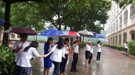 Thầy cô giáo ai nấy đều vui vẻ che chắn cho học trò dù là phải đứng dưới cơn mưa. (Ảnh: cô Nguyễn Thị Thanh Nhàn).