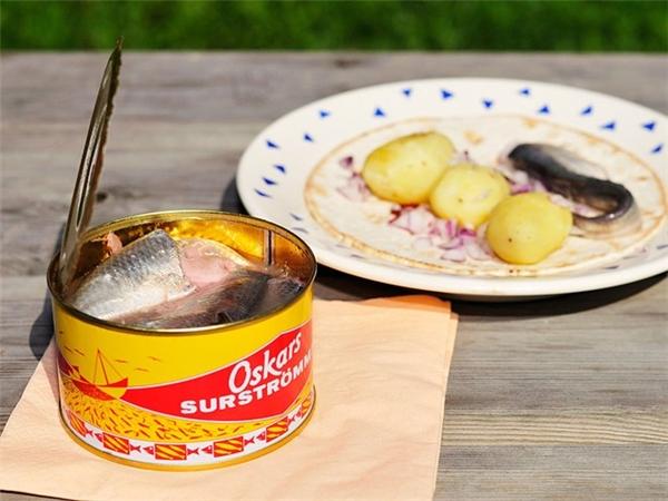 Surströmming (Thụy Điển): Món cá trích thối thách thức ngay cả những người can đảm nhất. Mùi của món Surströmming khó ngửi tới mức mọi người phải đem hộp cá ra ngoài trời mới dám mở. Ảnh: CNTraveler.
